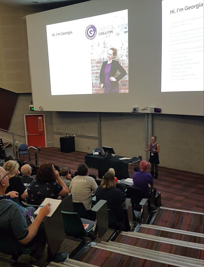 Georgia presenting a talk to crowd in lecture theatre